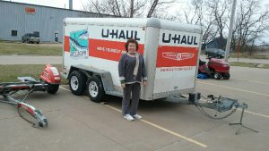 Photo of a dark-haired middle-aged woman standing in front of a U-Haul trailer.
