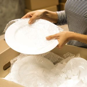 Hands holding a plate over a box full of bubble wrap.