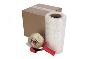 Packing supplies: cardboard box, bubble wrap roll, and packing tape dispenser.