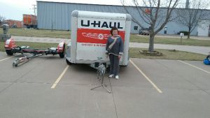 woman in front of rentable u-haul pull behind trailer