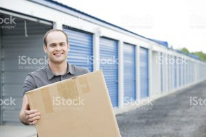 bald man holding moving box in front of self storage unit
